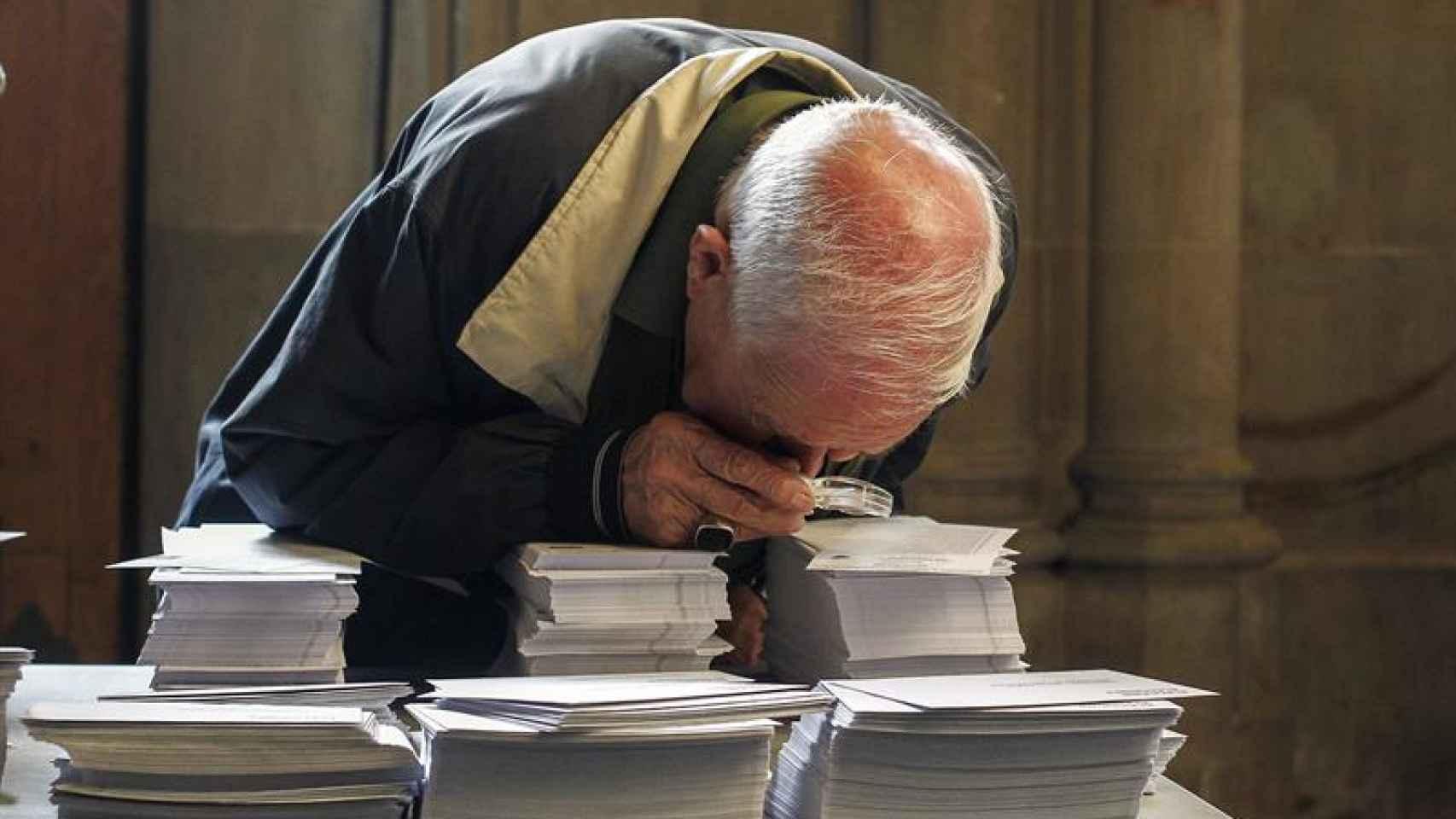 Un hombre observa con una lupa las papeletas de los diferentes partidos.