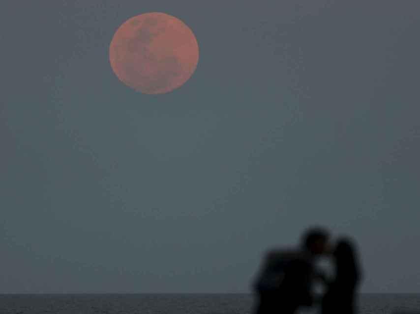 Una pareja se besa ante la luna roja sobre el Río de La Plata en Buenos Aires.