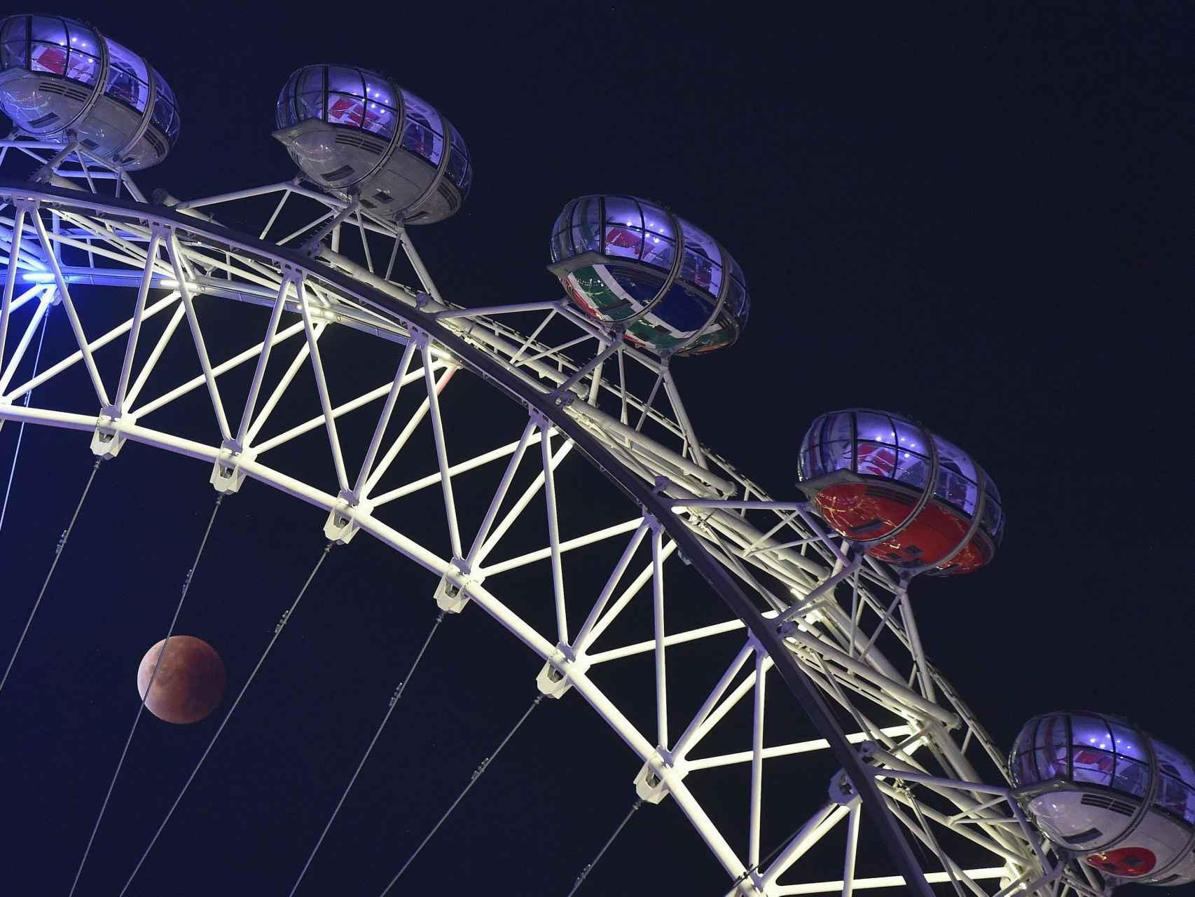 La luna a través de la noria London Eye.