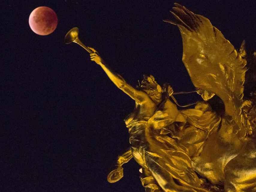 Artística imagen de la luna roja en París, entre las esculturas del Puente de Alejandro III.