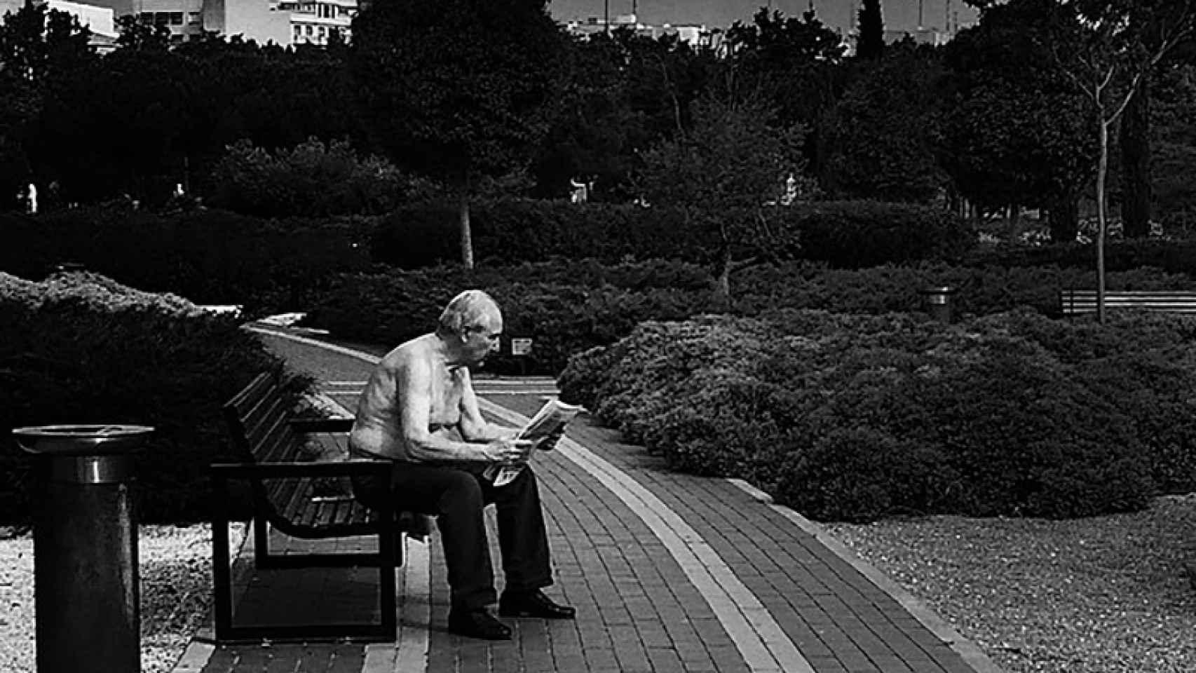 Un hombre lee el periódico en el banco de un parque