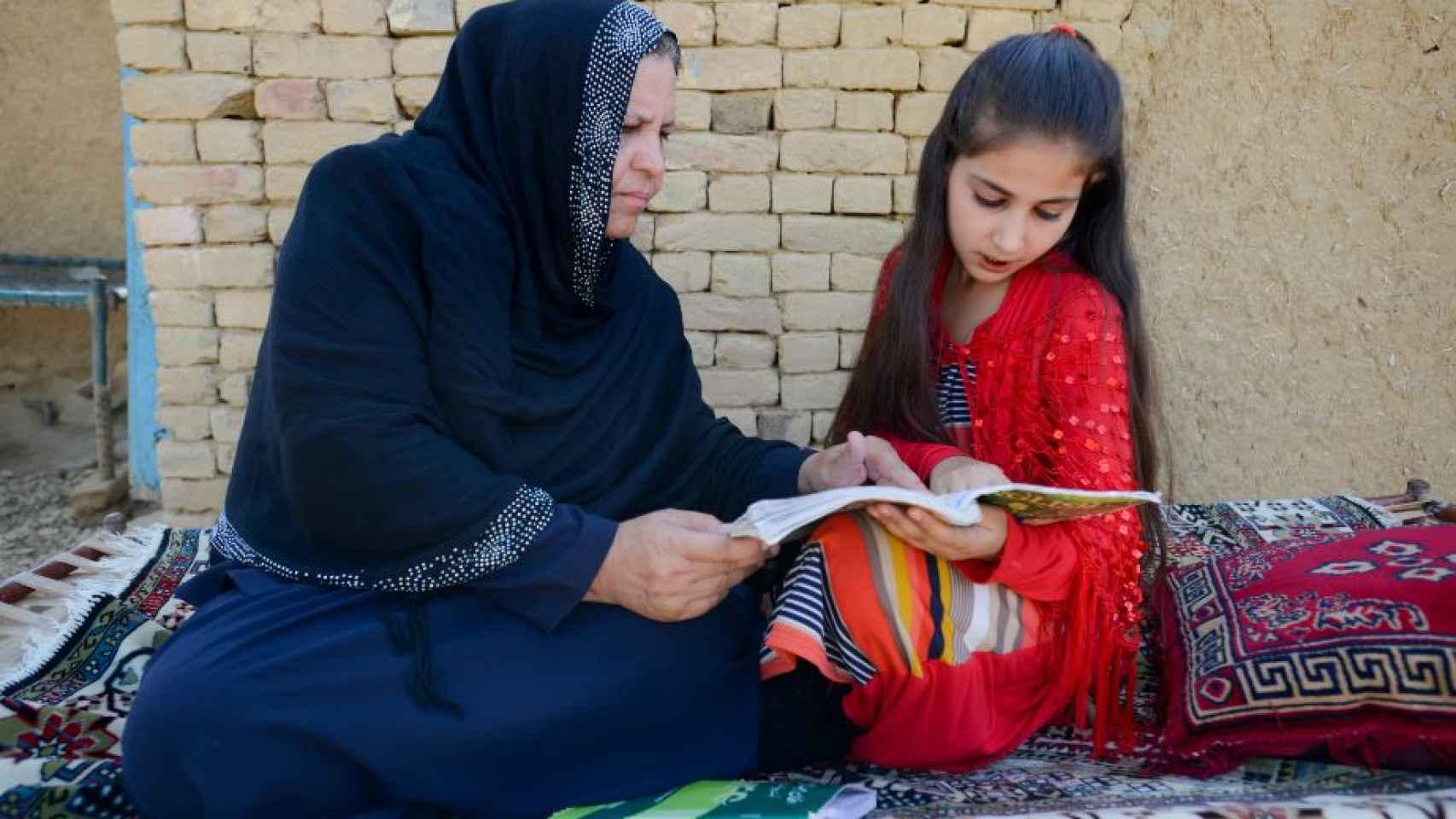 La profesora afgana Aqeela Asifi ayuda con los deberes a su hija pequeña Sawera.