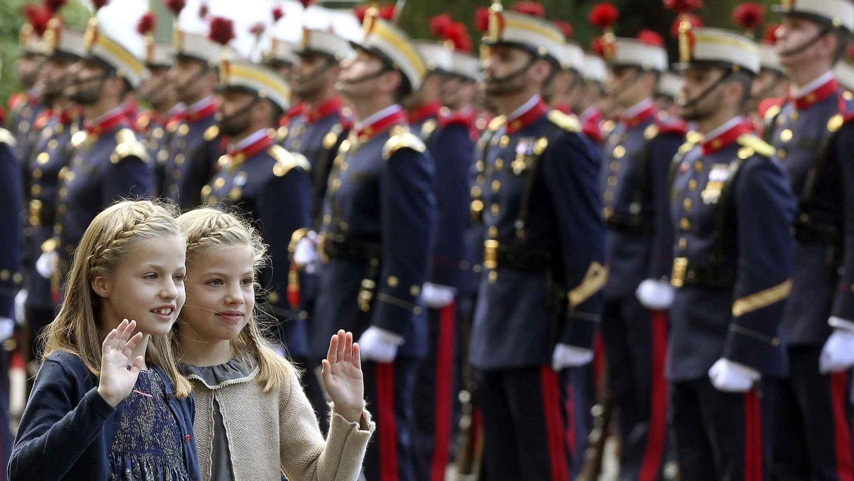 Las infantas saludan a su llegada al desfile.