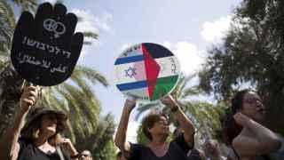 """Manifestantes israelíes progresistas muestran una pancarta que reza """"Ya basta de ocupación""""."""