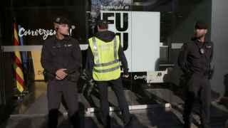 Agentes ante la fachada de la sede de CDC en Barcelona durante su registro este miércoles