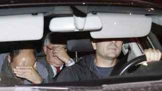 Un vehículo policial sale de la sede de CDC con el tesorero del partido, Andreu Viloca (en el centro), tras el registro de la sede de CDC