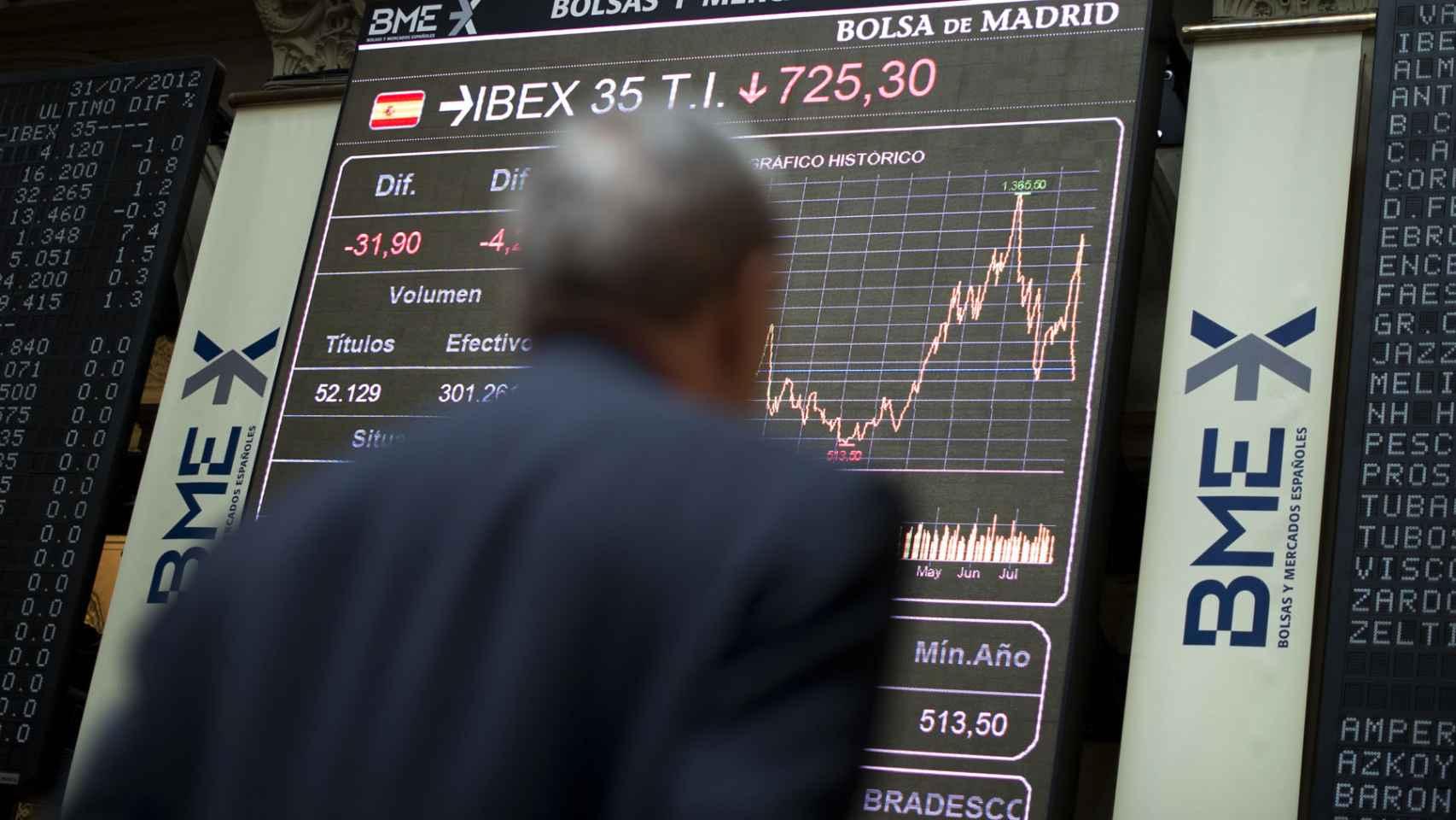 Un corredor mira la evolución de las inversiones en la Bolsa de Madrid.