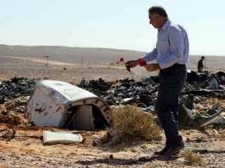 Un hombre deposita una flor junto a los restos de la aeronave.