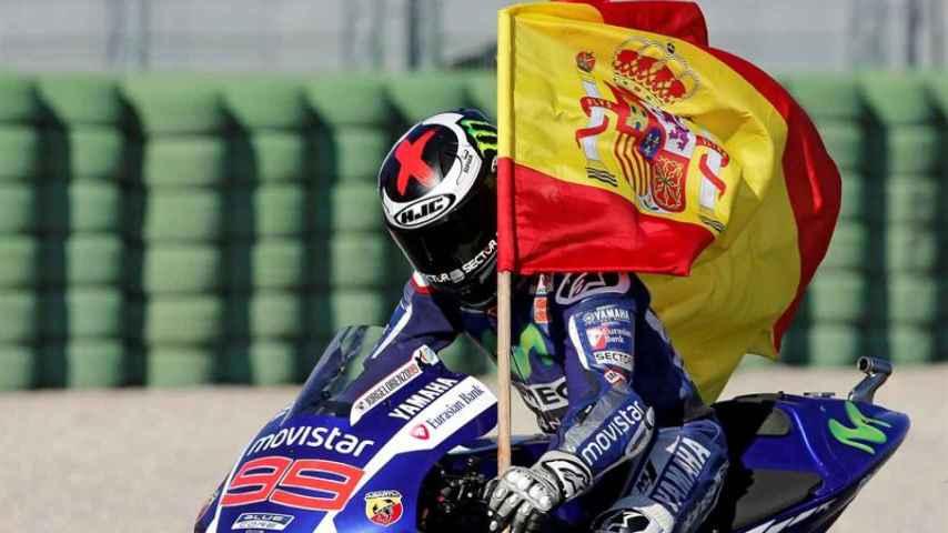 El piloto porta una bandera tras ganar la carrera.