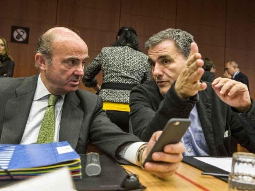 El ministro de Economía, Luis de Guindos, conversa durante el Eurogrupo con su colega griego, Euclides Tsakalotos
