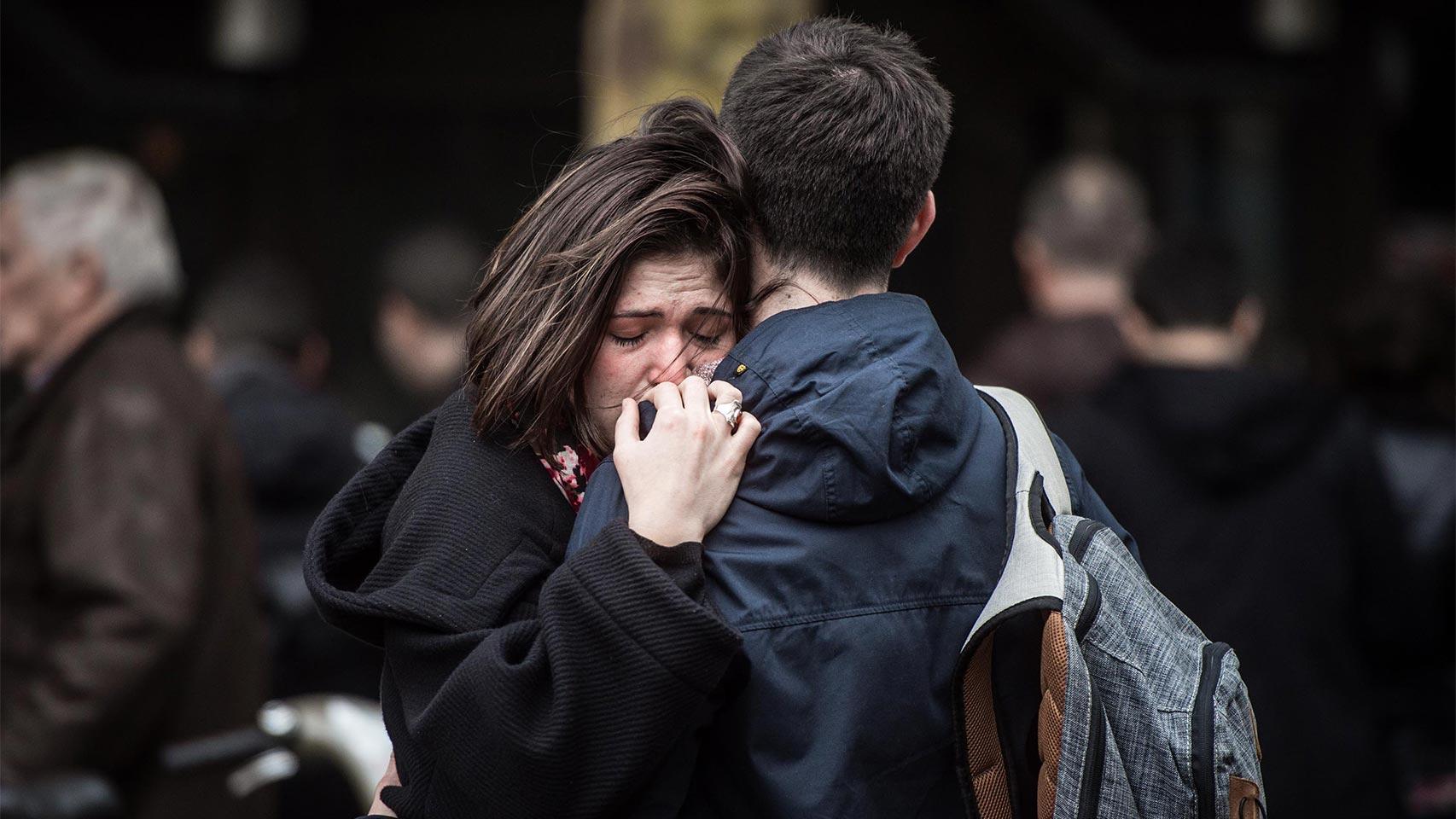 Una pareja se abraza cerca de uno de los cafés atacados.