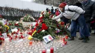Una mujer coloca flores cerca de la embajada francesa en Moscú