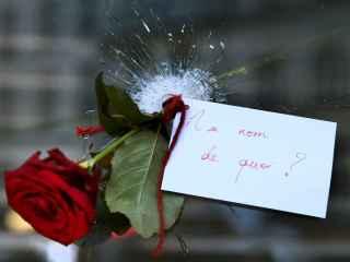 """Una rosa con mensaje en uno de los agujeros que dejaron las balas en uno de los restaurantes atacados: """"¿En nombre de qué?."""
