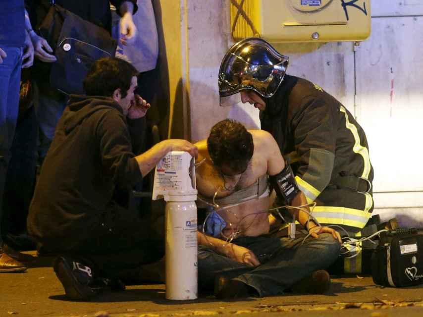 Los bomberos atienden a uno de los heridos. / Reuters