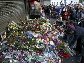 Varios ciudadanos muestran sus respetos en uno de los lugares de la tragedia en París.