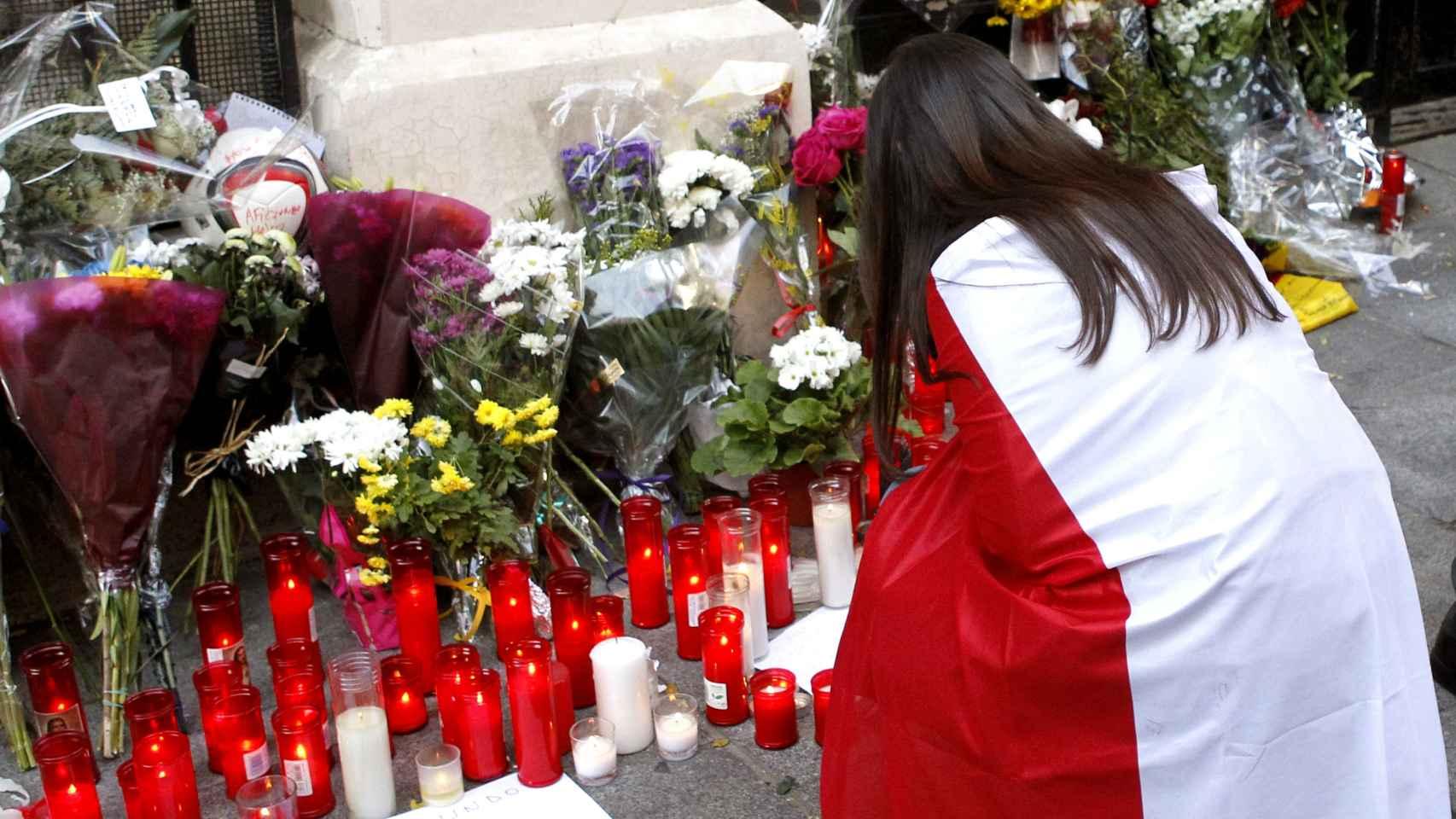 Una joven con la bandera francesa se solidariza con los ataques ante la embajada.