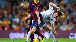 Andrés Iniesta y Luka Modric disputan un balón.