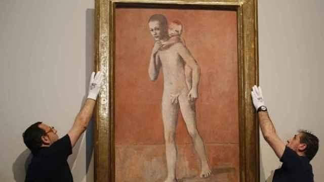 Dos operarios cuelgan uno de los Picassos expuestos en El Prado.