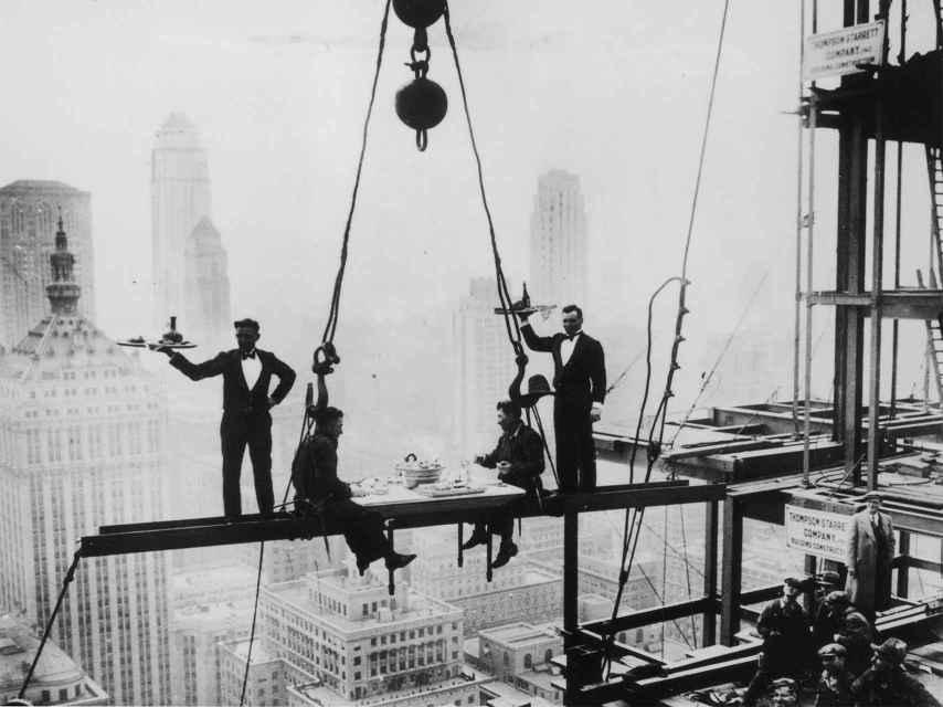 Dos camareros sirven el almuerzo a dos trabajadores, sobre el edificio Waldorf-Astoria (1930)