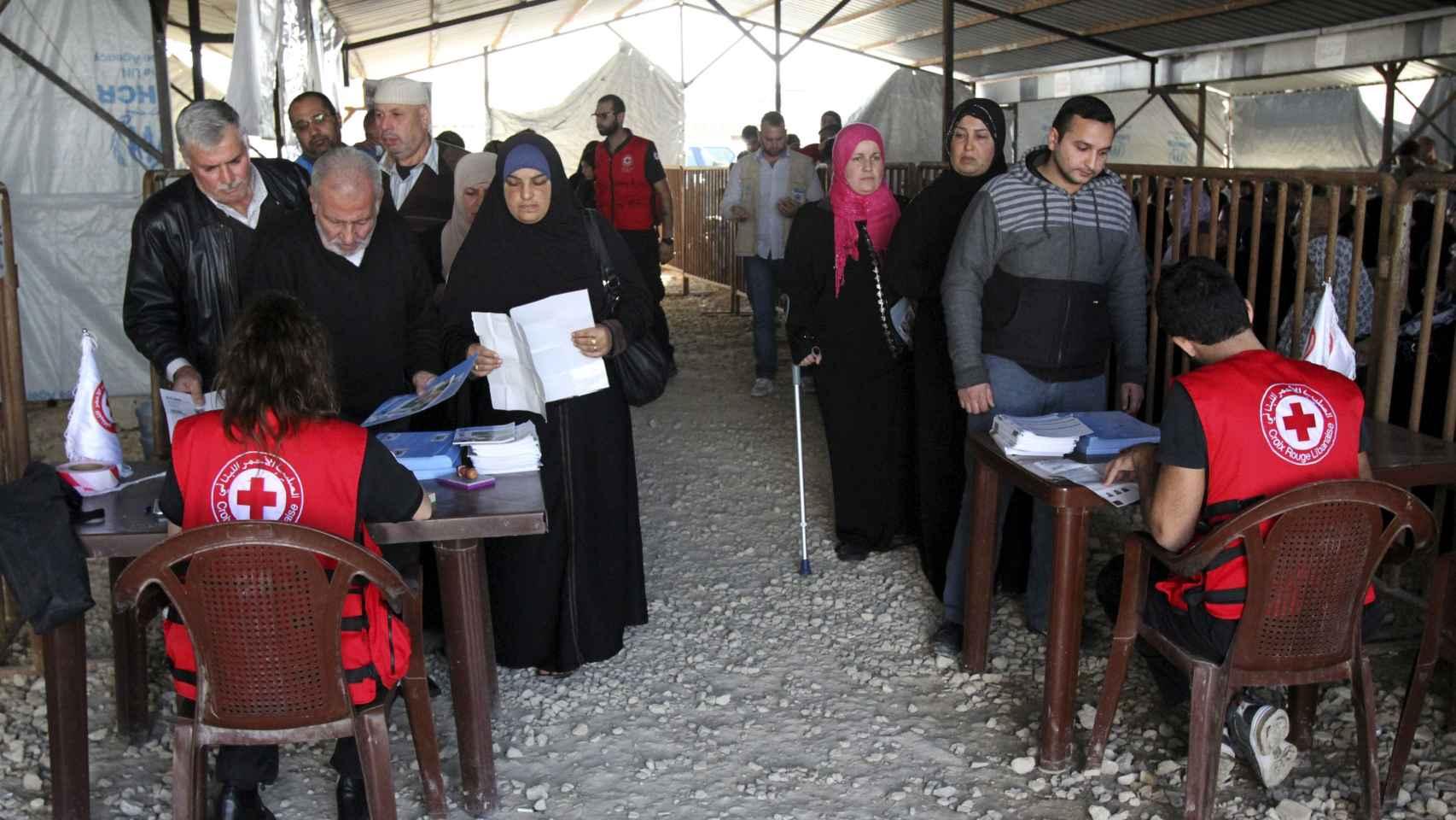 Refugiados sirios hacen cola en un centro de Acnur.