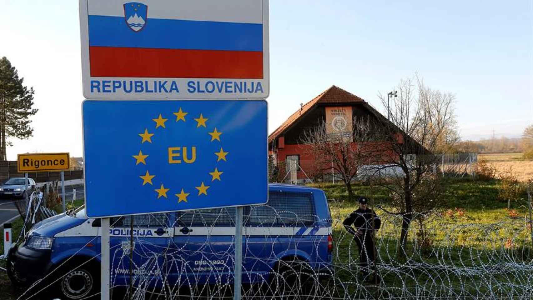 Policías eslovenos montan guardia junto a la valla levantada en su frontera con Croacia.