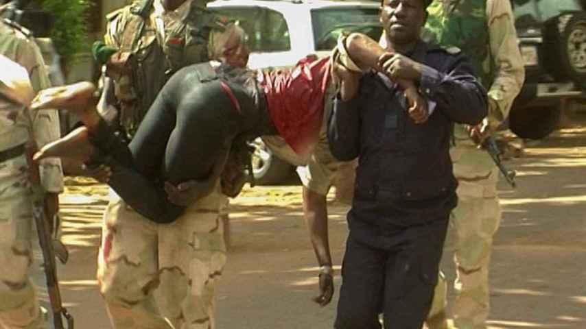 Militares de Mali trasladan a una mujer herida en el ataque. Efe
