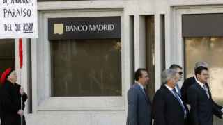 Un hombre protesta ante la sede del Banco de Madrid.