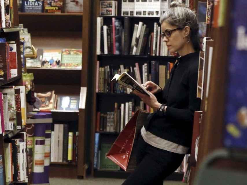 Una mujer leyendo en una librería.