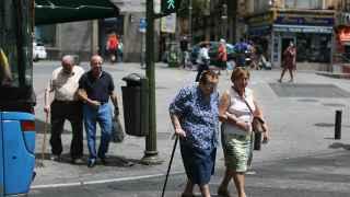 Una mujer, ayudada a cruzar la calle.
