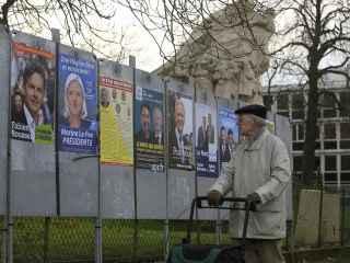 Un ciudadano francés pasea ante los carteles electorales.