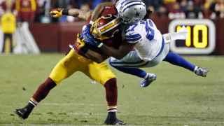 Wilcox de los Cowboys intenta placar a Thompson, de los Redskins.