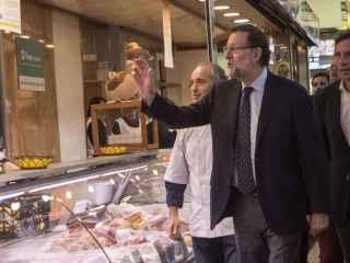 Mariano Rajoy junto al número uno de la lista del PP balear al Congreso, Mateo Isern, en su visita al mercado del Olivar en Mallorca