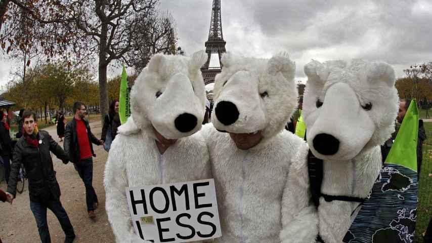 Tres manifestantes disfrazados de osos polares, ayer en París.