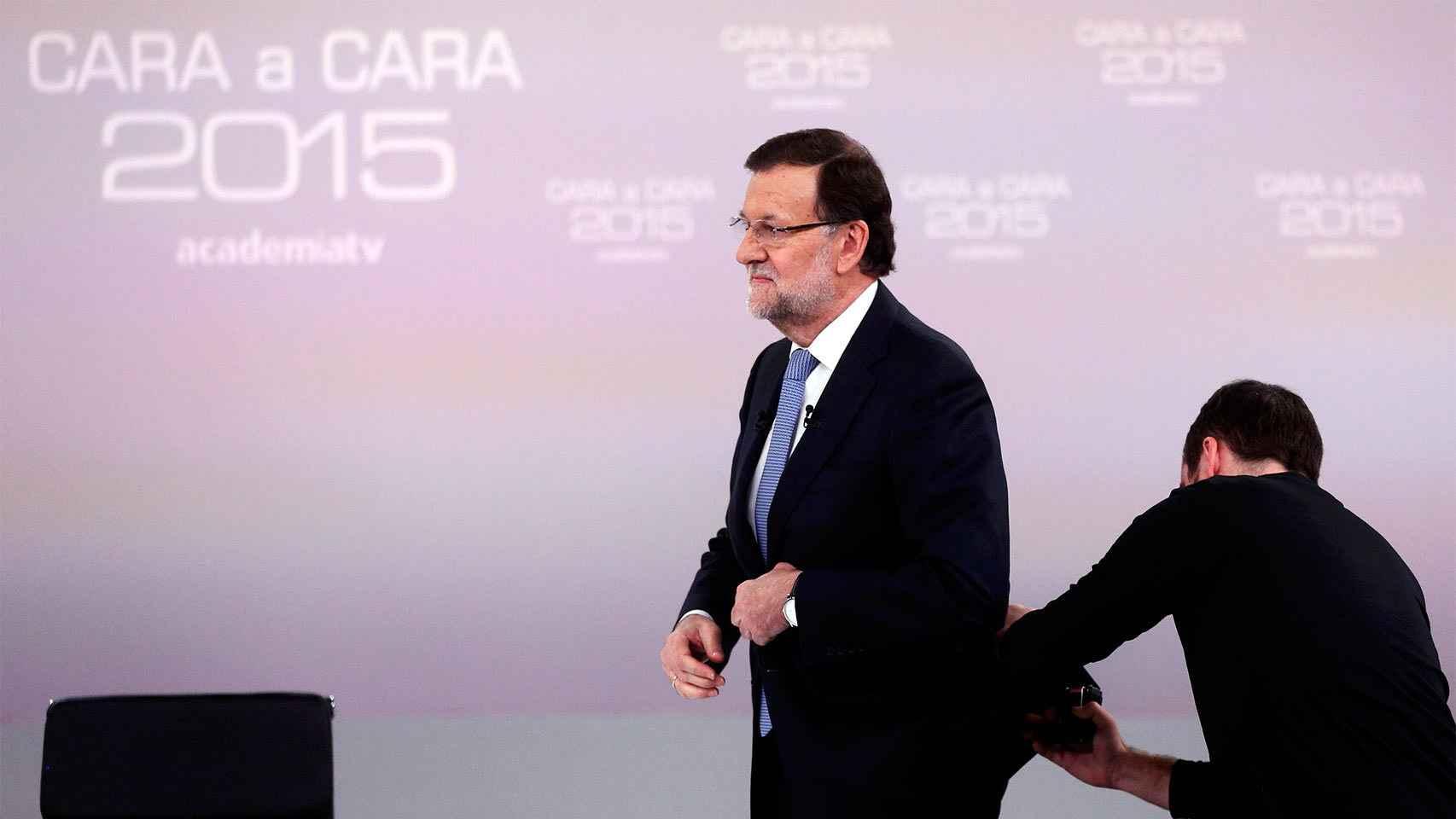 Un operador coloca el micrófono a Rajoy.