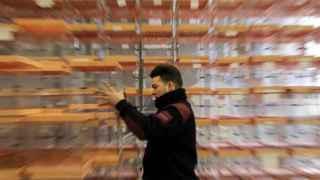 Un trabajador mueve varias urnas en los talleres municipales donde se almacenan las urnas de Barcelona