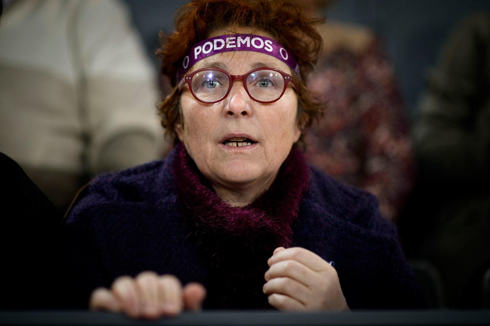 Una mujer sigue un discurso de Pablo Iglesias.