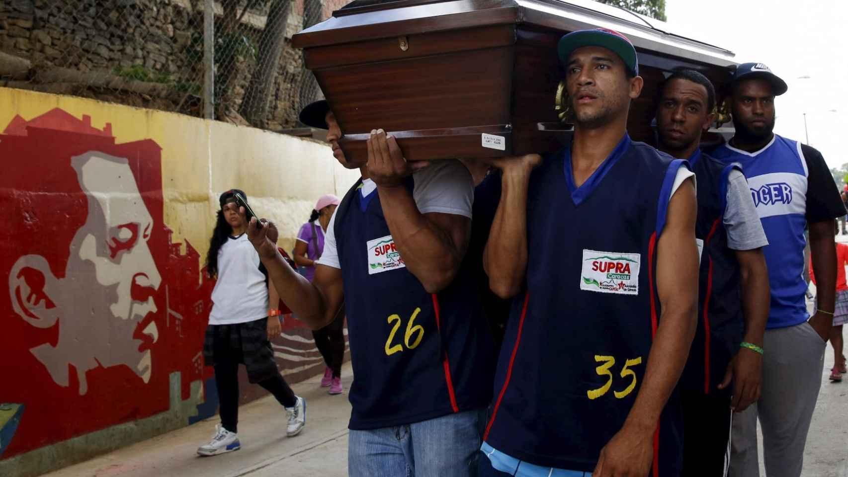 Compañeros de un jugador de baloncesto víctima de un crimen en Caracas portan su féretro.