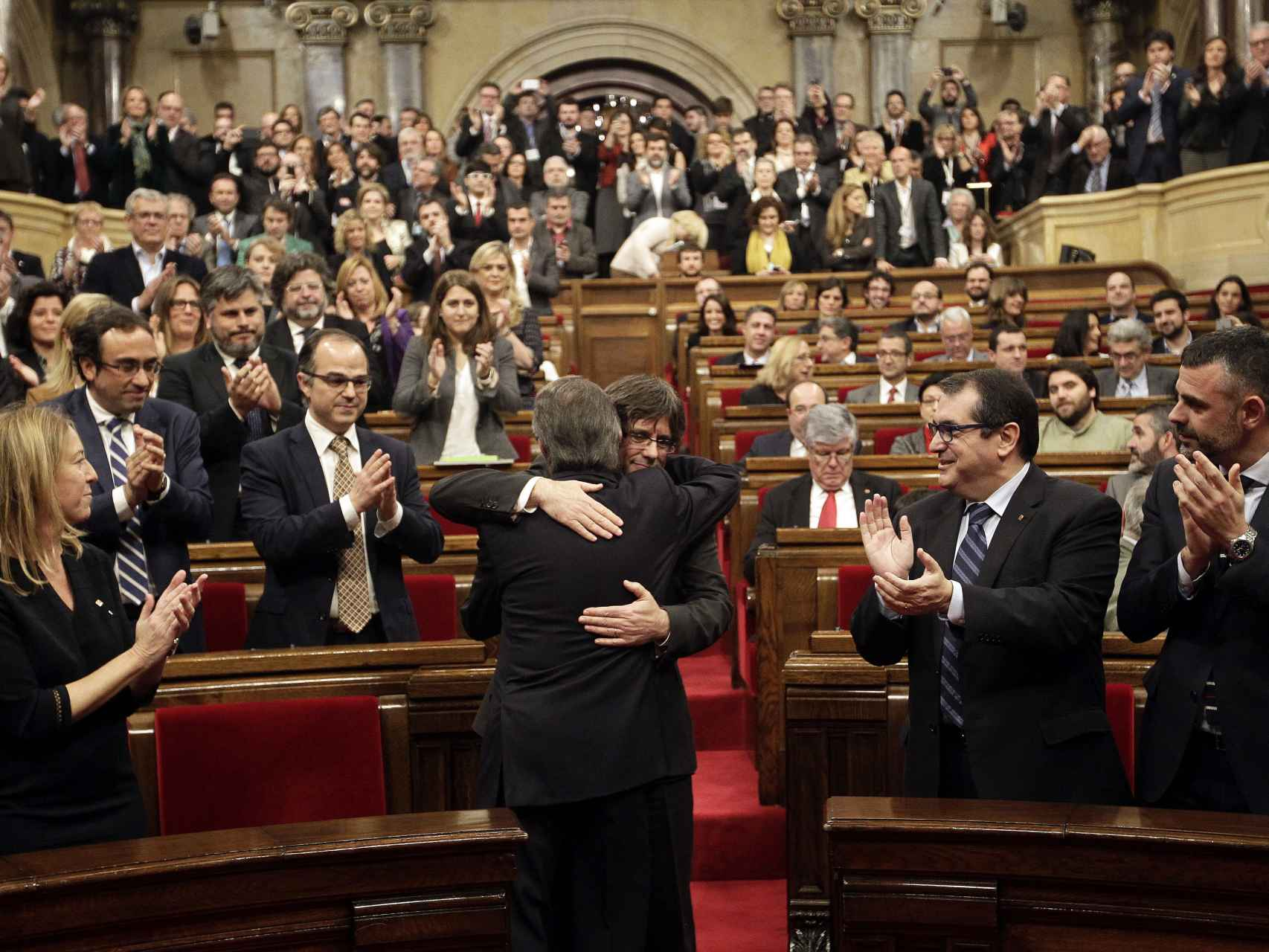 El Parlament aplaude el abrazo entre Mas y Puigdemont.