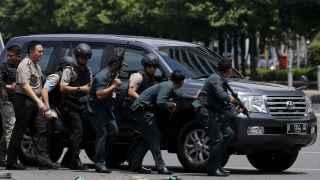 LA policía indonesa, con rifles y resguardados tras un coche.