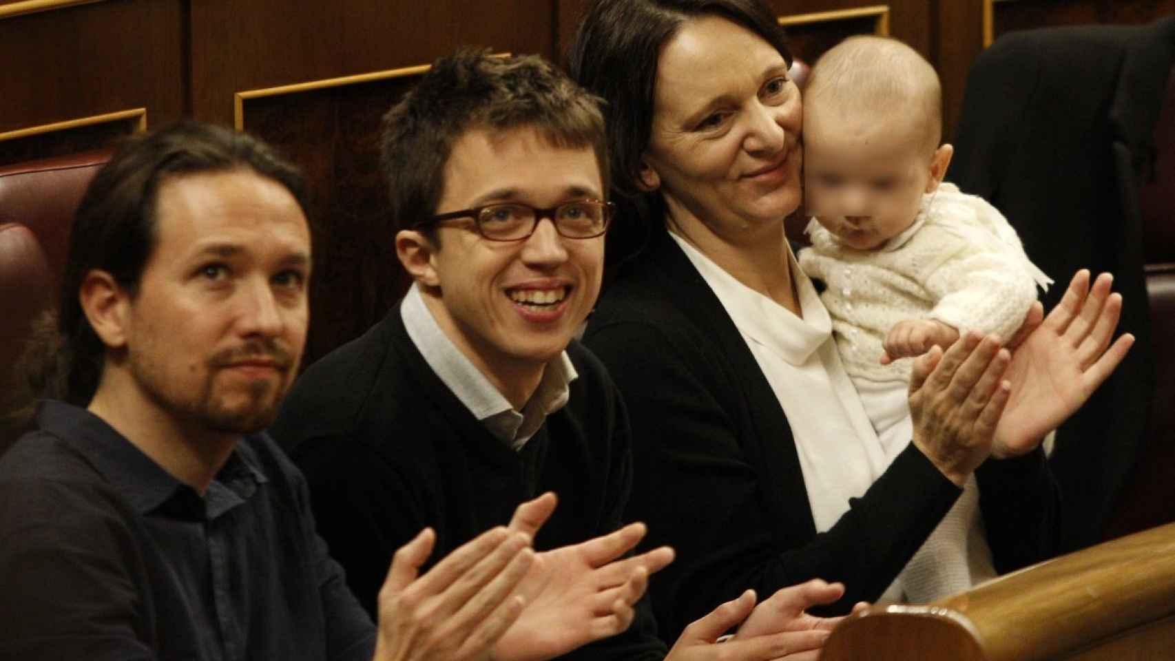 Carolina Bescansa sujeta en brazos a su bebé, con Iñijo Errejón y Pablo Iglesias a su lado.