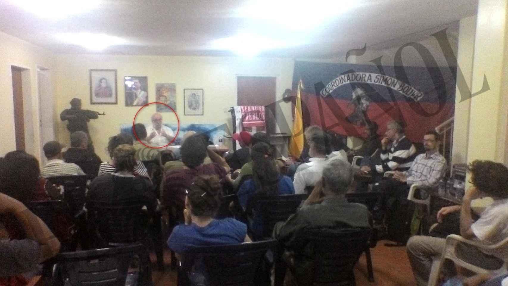 Iñaki Gil habla junto a un busto armado y la bandera de la Coordinadora Simón Bolívar.
