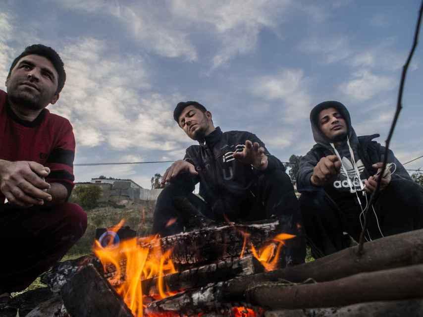 Un grupo de universitarios kurdos hacen una fogata a las afueras del CETI.