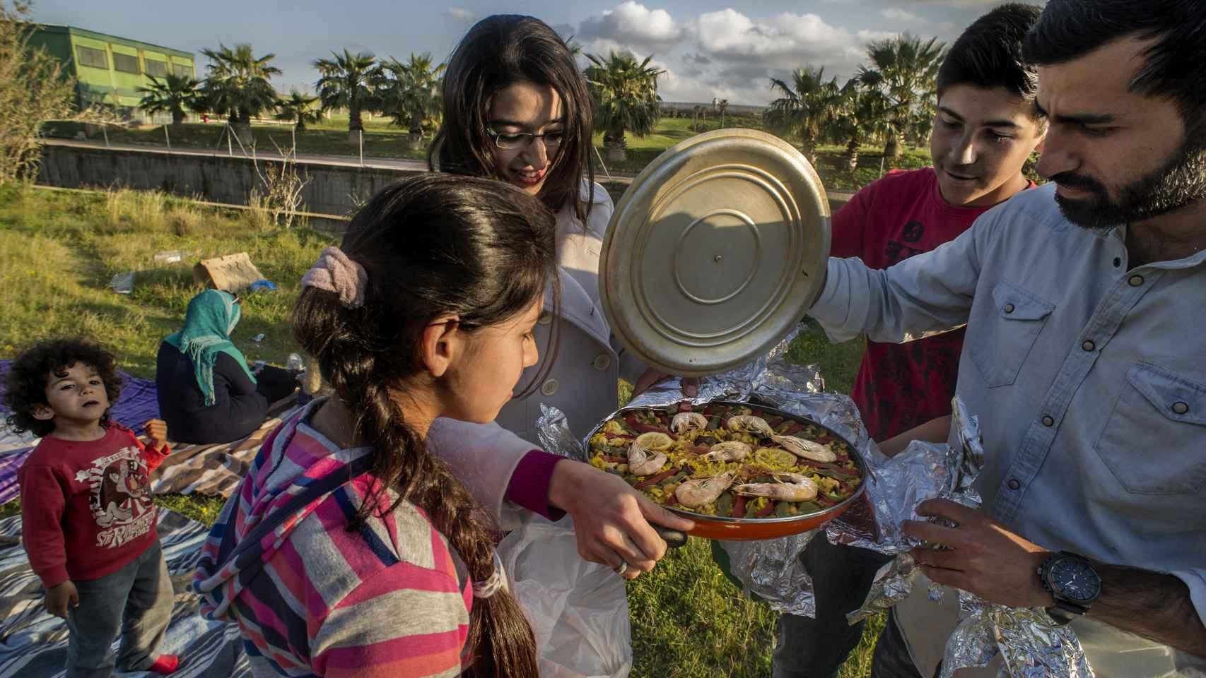 Lamya y Saleh, junto a la familia, preparando una paella.