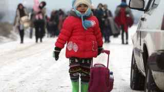Refugiados sirios, iraquíes y afganos caminan en la frontera entre Serbia y Macedonia.