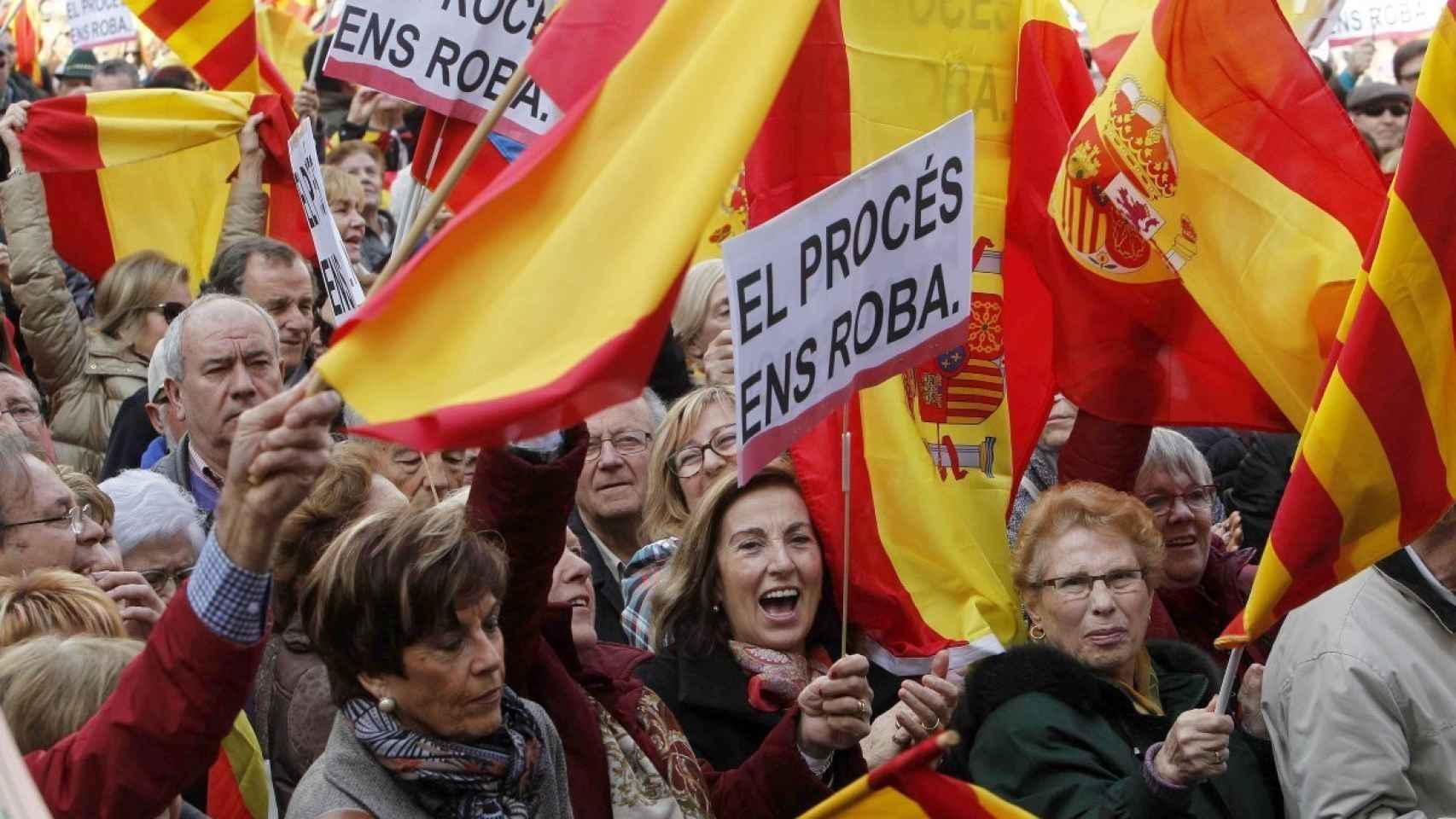 Manifestantes con pancartas en las que se lee 'El procés ens roba'.