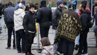 Refugiados en el exterior de una de las dependencias para pedir documentación.