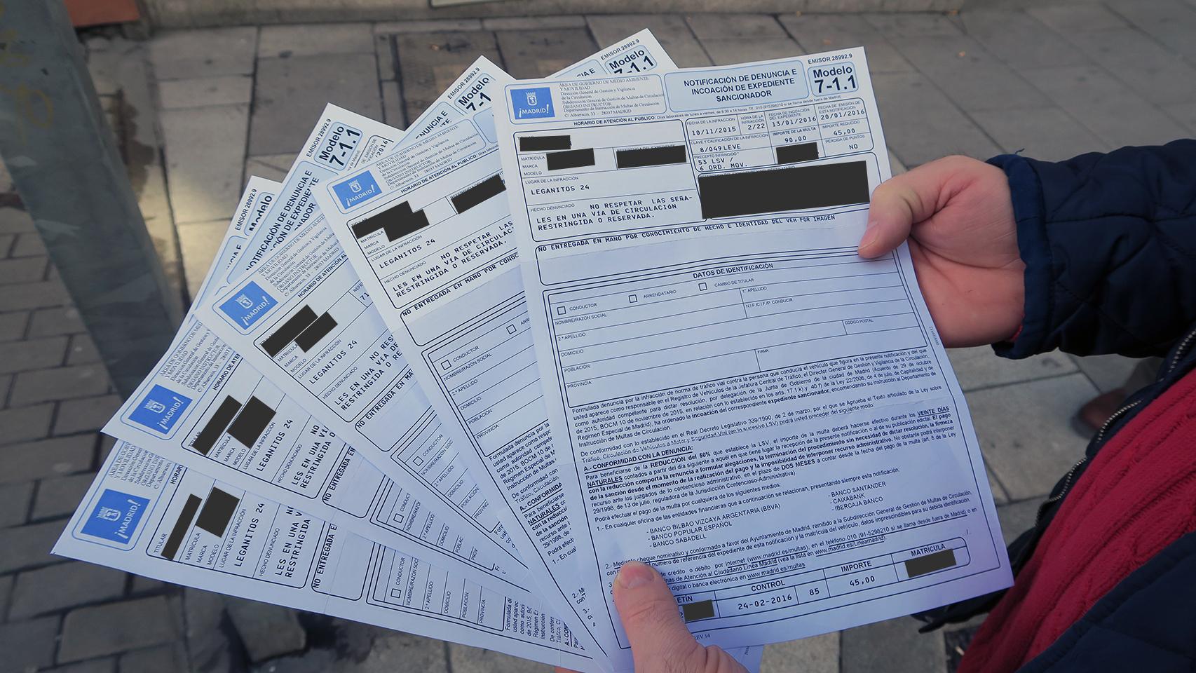 Un afectado muestra cinco de sus siete multas en la calle Leganitos de Madrid