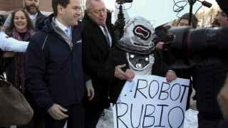 Manifestantes vestidos de robot abordan al candidato Marco Rubio.