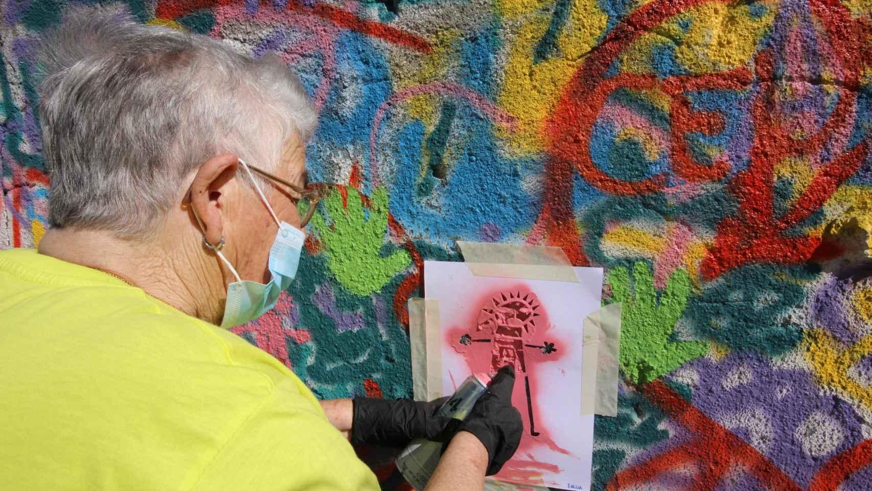 Una de las ancianas dibujando con plantilla y spray