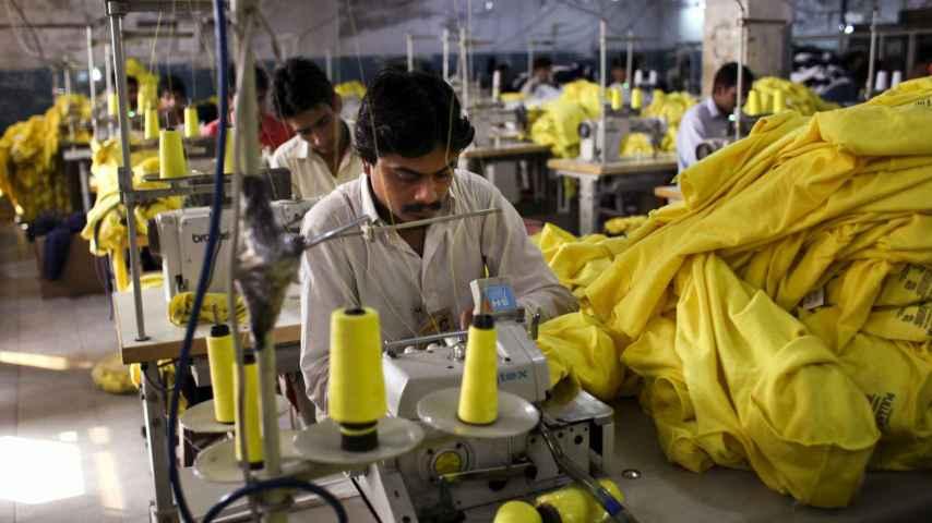 Trabajadores cosen camisetas fabricadas para Inditex en una fábrica en Pakistán.